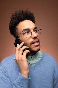 Giovane uomo d'affari di razza mista in occhiali e abbigliamento casual intelligente che tiene lo smartphone all'orecchio durante una chiamata d'affari
