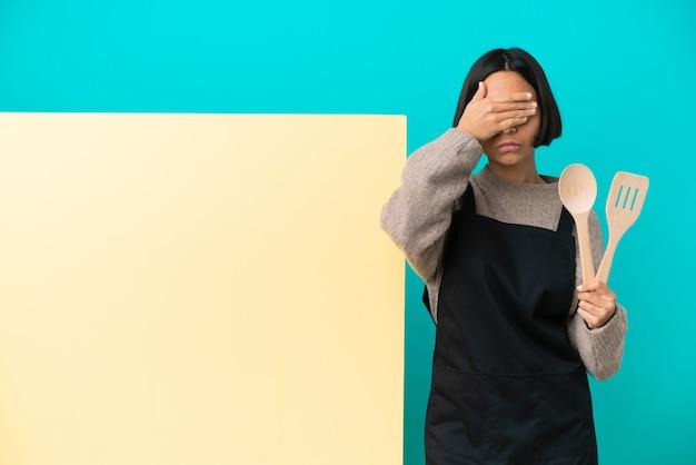 Giovane donna di razza mista cuoco con un grande cartello isolato su sfondo blu che copre gli occhi con le mani. non voglio vedere qualcosa