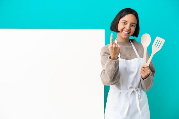 Giovane donna di razza mista cuoco con un grande cartello isolato su sfondo blu facendo gesto in arrivo