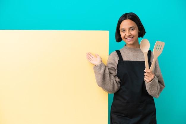 Giovane cuoca di razza mista con un grande cartello isolato su sfondo blu che allunga le mani di lato per invitare a venire
