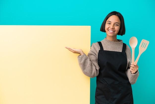 Giovane donna cuoca di razza mista con un grande cartellone isolato su sfondo blu che tiene immaginario copyspace sul palmo per inserire un annuncio