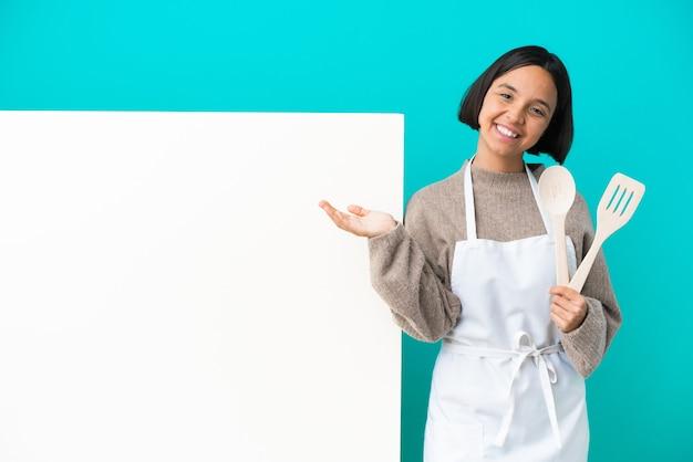 Giovane cuoca di razza mista con un grande cartello isolato su sfondo blu che presenta e invita a venire con la mano