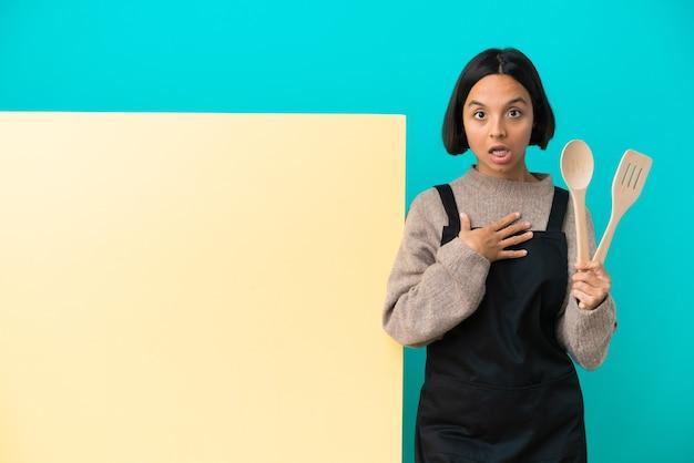 Giovane donna cuoca di razza mista con un grande cartello isolato su sfondo blu sorpreso e scioccato mentre guarda a destra
