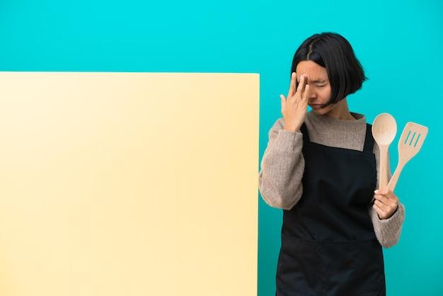 Giovane donna cuoca di razza mista con un grande cartello isolato su sfondo blu con mal di testa