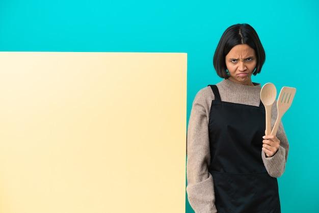 Giovane donna cuoca di razza mista con un grande cartello isolato su sfondo blu con espressione infelice