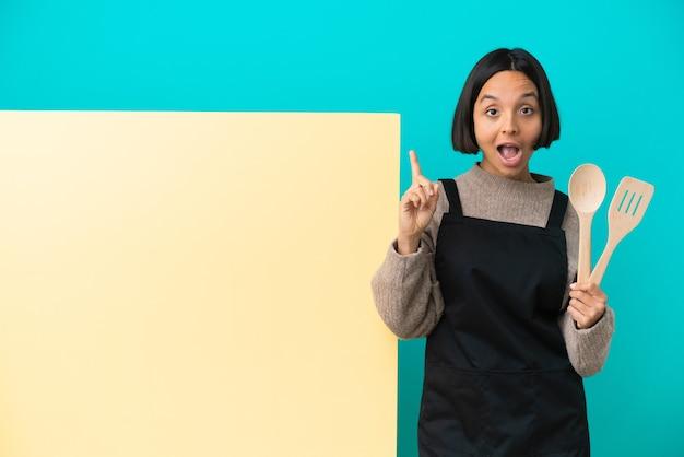 Giovane cuoca di razza mista con un grande cartello isolato con l'intenzione di realizzare la soluzione sollevando un dito