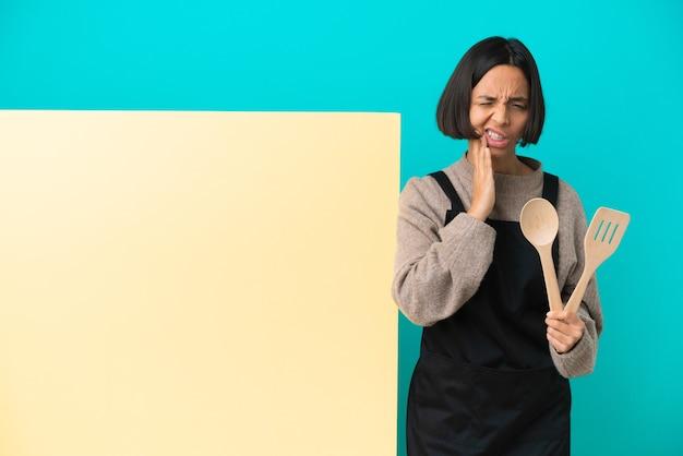 Giovane donna cuoca di razza mista con un grande cartello isolato con mal di denti