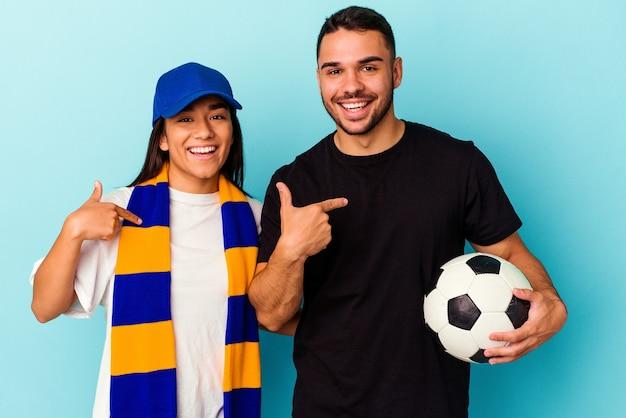 Giovane coppia di razza mista che pulisce casa isolata su sfondo blu persona che punta a mano a uno spazio copia camicia, orgoglioso e fiducioso