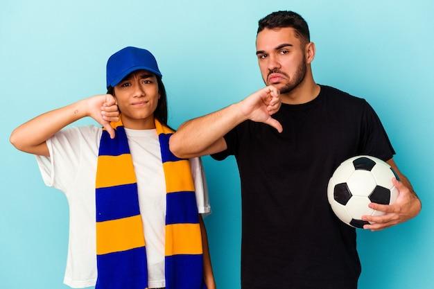 Giovane coppia di razza mista che pulisce casa isolata su sfondo blu che mostra un gesto di antipatia, pollice verso. concetto di disaccordo.