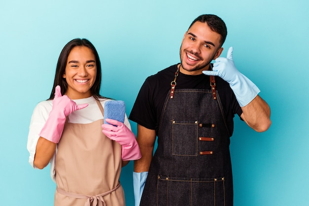 Giovani coppie della corsa mista che puliscono casa isolata su fondo blu che mostra un gesto di chiamata del telefono cellulare con le dita.