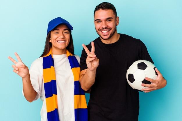 Giovane coppia di razza mista che pulisce casa isolata su sfondo blu che mostra il numero due con le dita.