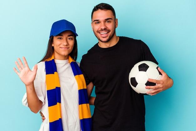 Giovane coppia di razza mista che pulisce casa isolata su sfondo blu sorridente allegro che mostra il numero cinque con le dita.