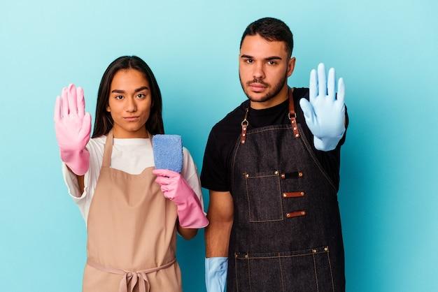 Giovane coppia di razza mista che pulisce casa isolata su sfondo blu in piedi con la mano tesa che mostra il segnale di stop, impedendoti.
