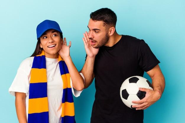 Giovani coppie della corsa mista che puliscono casa isolata su fondo blu che prova ad ascoltare un gossip.