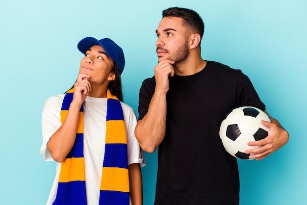Giovane coppia di razza mista che pulisce casa isolata sul blu guardando lateralmente con espressione dubbiosa e scettica.