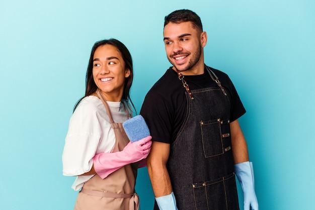 La giovane coppia di razza mista che pulisce la casa isolata sul blu sembra da parte sorridente, allegra e piacevole.