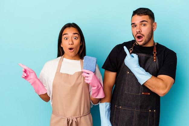 Giovane coppia di razza mista che pulisce casa isolata sul blu che punta al lato