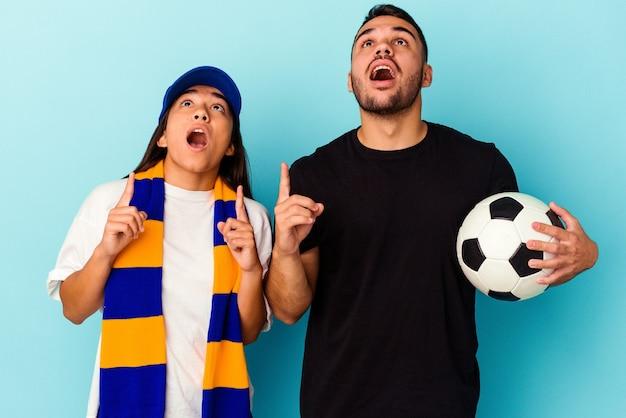 Giovane coppia di razza mista che pulisce casa isolata sul blu che punta al rialzo con la bocca aperta.
