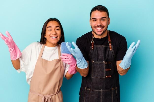 Giovane coppia di razza mista che pulisce casa isolata sul blu ricevendo una piacevole sorpresa, eccitata e alzando le mani.
