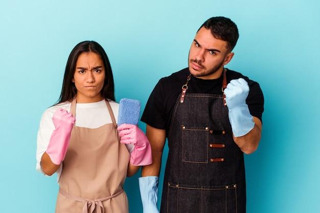 Giovani coppie della corsa mista che puliscono casa isolata sul pugno blu che mostra, espressione facciale aggressiva.