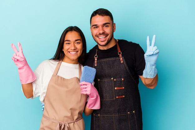 Giovane coppia di razza mista che pulisce casa isolata sul blu che mostra il numero due con le dita.
