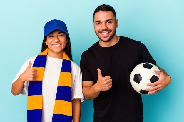 Giovane coppia di razza mista che pulisce casa isolata sul blu sorridendo e alzando il pollice thumb