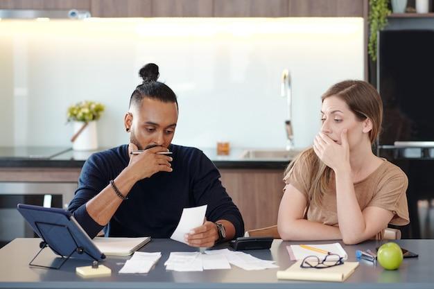 Giovane coppia di razza mista che copre la bocca mentre è scioccata dalla somma in fattura non pagata