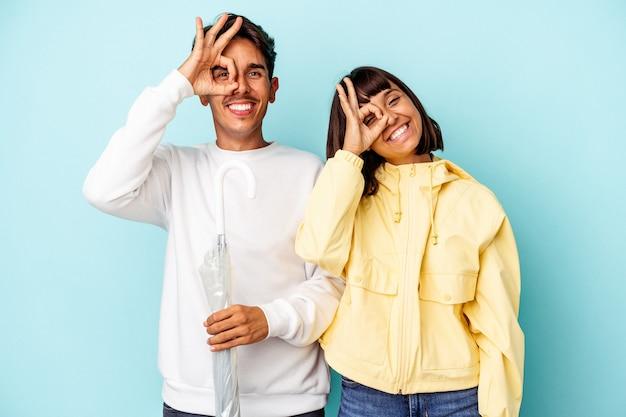 Giovane coppia di razza mista che tiene ombrello isolato su sfondo blu eccitato mantenendo il gesto ok sull'occhio.