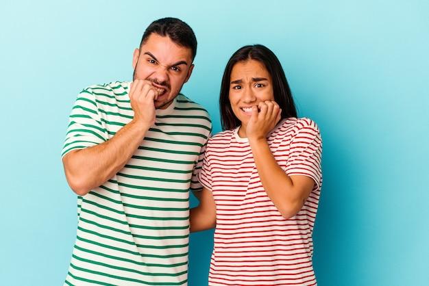 Giovane coppia di razza mista isolata su unghie blu mordaci, nervosa e molto ansiosa.