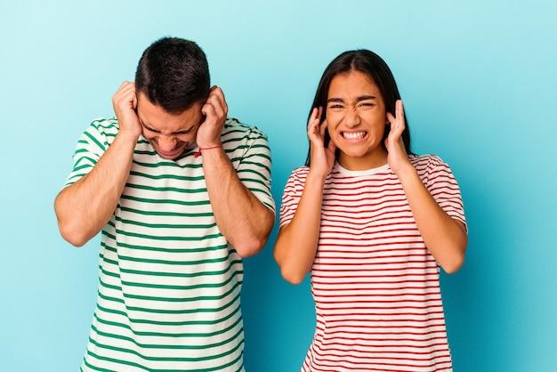 Giovani coppie della corsa mista isolate sulle orecchie blu della copertura con le mani.