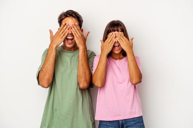 La giovane coppia di razza mista isolata su sfondo bianco copre gli occhi con le mani, sorride ampiamente in attesa di una sorpresa.