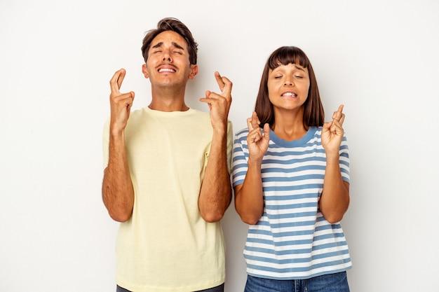 Giovane coppia di razza mista isolata su sfondo bianco incrociando le dita per avere fortuna