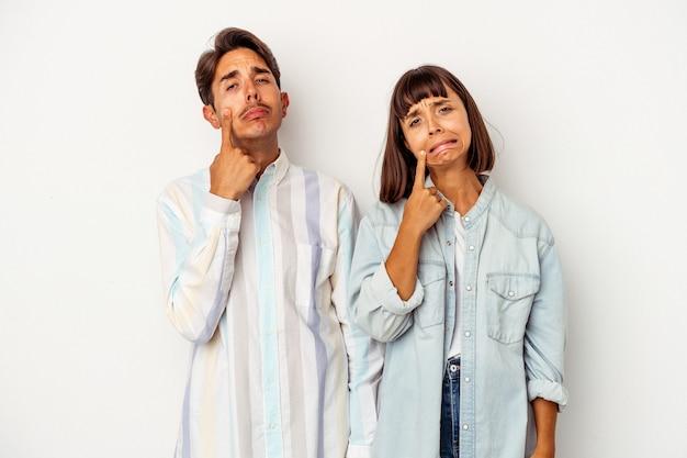 Giovane coppia di razza mista isolata su sfondo bianco che piange, infelice con qualcosa, agonia e concetto di confusione.
