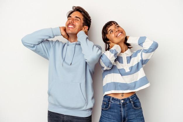 Giovane coppia di razza mista isolata su sfondo bianco sentirsi sicuri, con le mani dietro la testa.