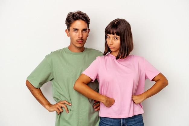Giovane coppia di razza mista isolata su sfondo bianco accigliato il viso per il dispiacere, tiene le braccia conserte.