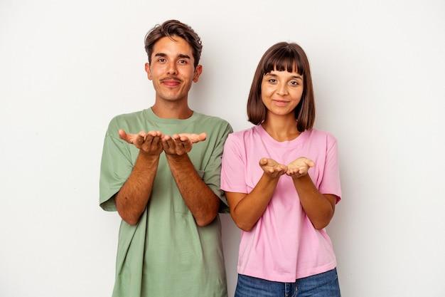 Giovane coppia di razza mista isolata su sfondo bianco che tiene qualcosa con le palme, offrendo alla macchina fotografica.
