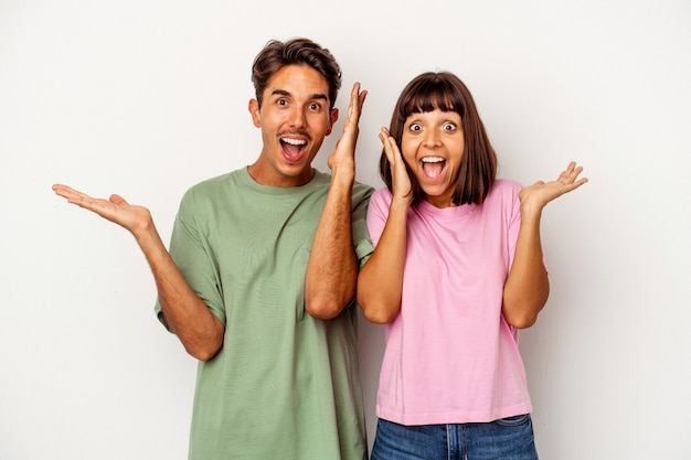 La giovane coppia di razza mista isolata su sfondo bianco tiene lo spazio della copia su un palmo, tiene la mano sulla guancia. stupito e deliziato.