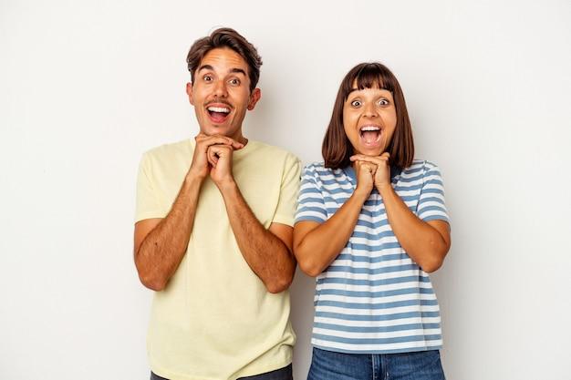 Giovane coppia di razza mista isolata su sfondo bianco pregando per la fortuna, stupita e aprendo la bocca guardando in avanti.