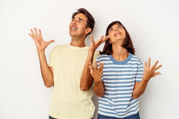 Giovane coppia di razza mista isolata su sfondo bianco che urla al cielo, alzando lo sguardo, frustrata.
