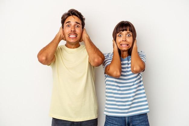 Giovane coppia di razza mista isolata su sfondo bianco urlando di rabbia.