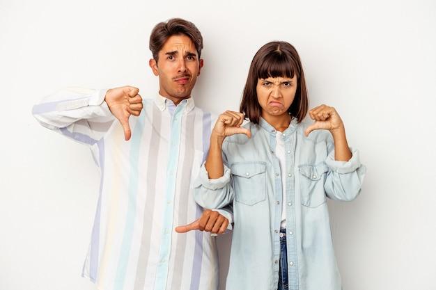 Giovane coppia di razza mista isolata su sfondo bianco che mostra il pollice verso il basso, concetto di delusione.