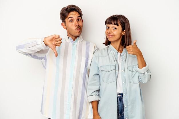 Giovane coppia di razza mista isolata su sfondo bianco che mostra pollice in alto e pollice in basso, difficile scegliere concept