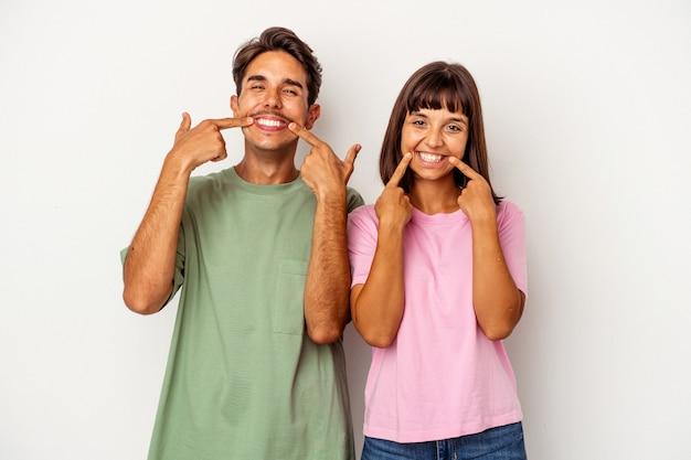 Giovane coppia di razza mista isolata su sfondo bianco sorride, puntando il dito alla bocca.