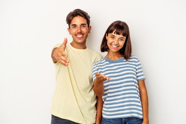 Giovani coppie della corsa mista isolate su fondo bianco che allungano la mano alla macchina fotografica nel gesto di saluto.