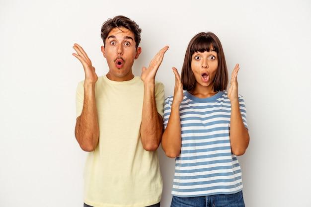 Giovane coppia di razza mista isolata su sfondo bianco sorpreso e scioccato.