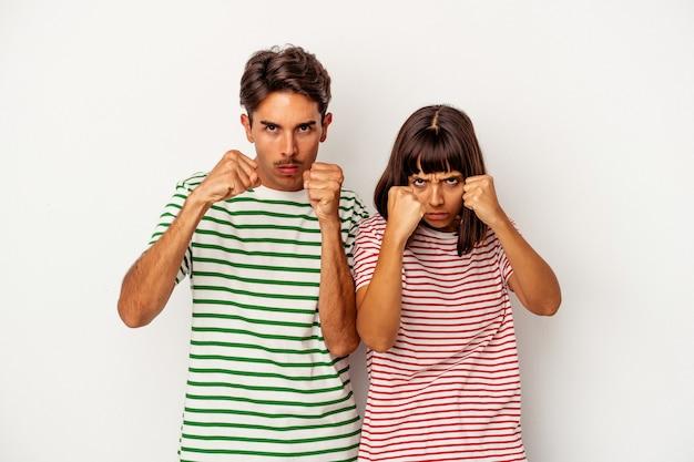 Giovane coppia di razza mista isolata su sfondo bianco che lancia un pugno, rabbia, combattimento a causa di una discussione, boxe.