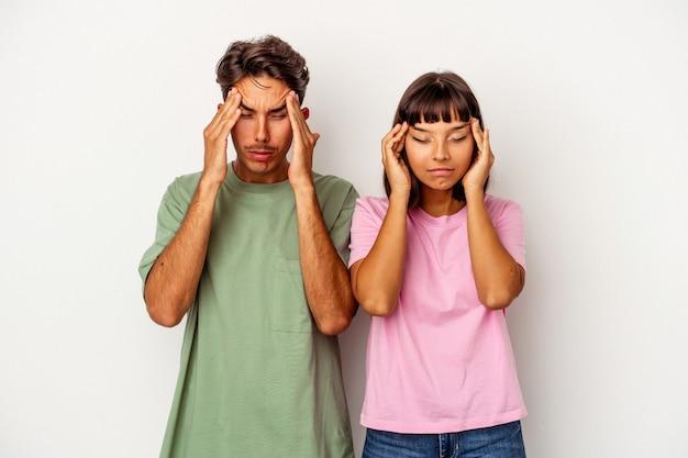 Giovane coppia di razza mista isolata su sfondo bianco toccando le tempie e avendo mal di testa.