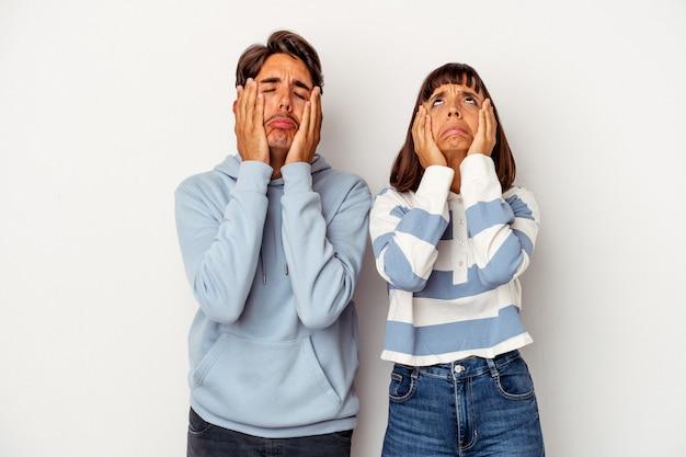 Giovane coppia di razza mista isolata su sfondo bianco piagnucolando e piangendo sconsolato.