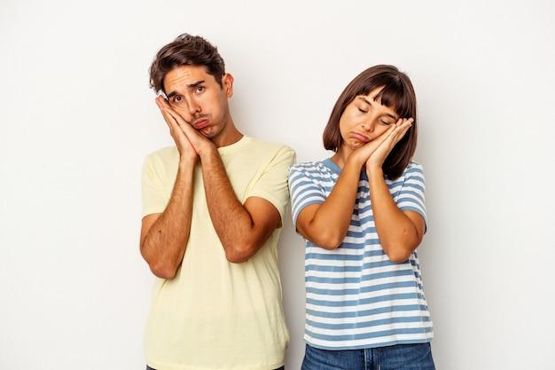 Giovane coppia di razza mista isolata su sfondo bianco che sbadiglia mostrando un gesto stanco che copre la bocca con la mano.