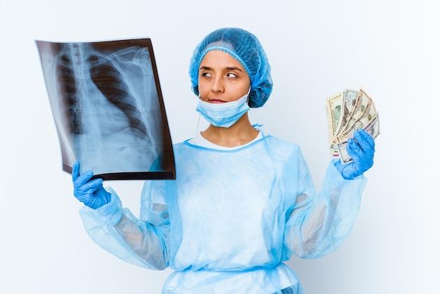 Giovane donna medico di razza mista che tiene i dollari isolati